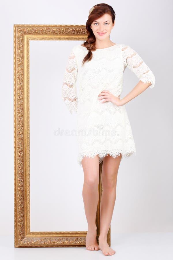 De mooie vrouw in kleding bevindt zich dichtbij frame stock afbeeldingen