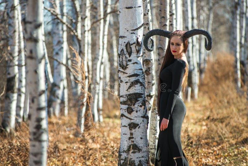 De mooie vrouw kleedde zich als feeheks in regenjas en met hoornen voor Halloween stock foto's