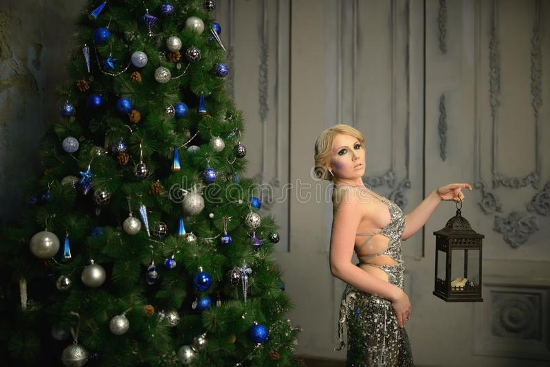 De mooie vrouw kleedde zich in seksuele de lantaarn dichtbij verfraaid van de avondjurkheks Kerstboom stock foto's