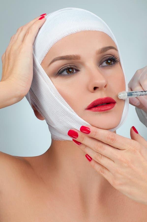 De mooie vrouw krijgt injectie in lippen met verbonden gezicht Schoonheid, Manier en Plastische chirurgieconcept stock fotografie