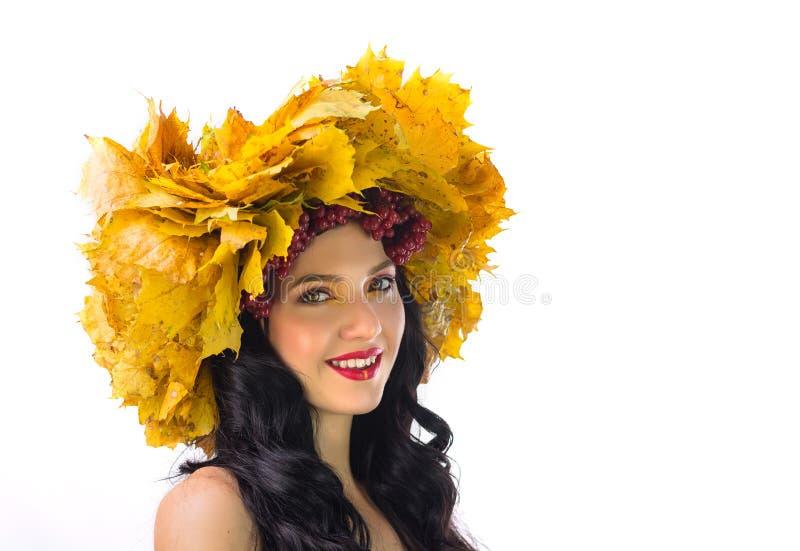De mooie vrouw in kroon van de herfstbladeren en guelder-nam op w toe stock foto's