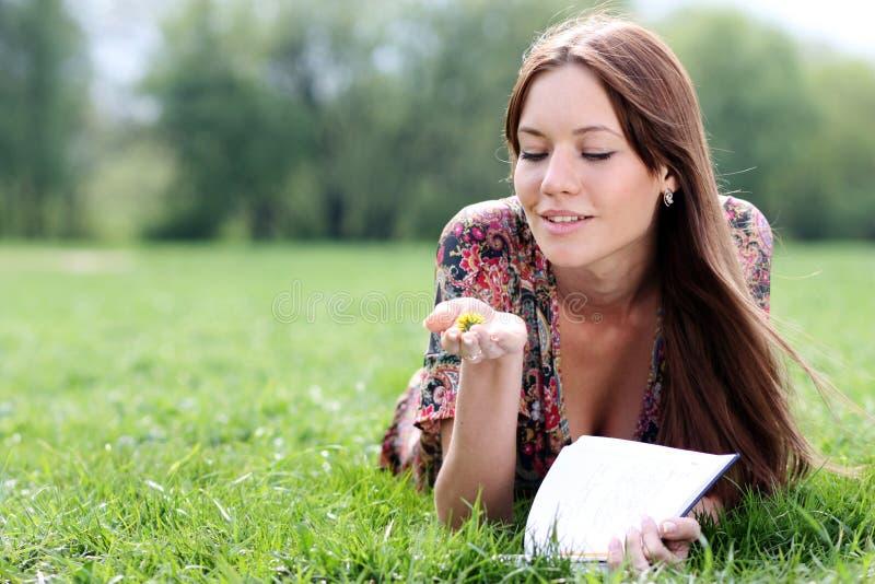 de mooie vrouw legt op een gras in park met een agenda in Ha royalty-vrije stock afbeeldingen