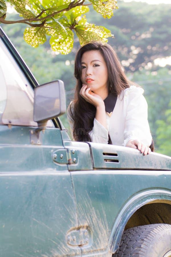 De mooie vrouw leunt op de auto, bekijkend camera stock foto