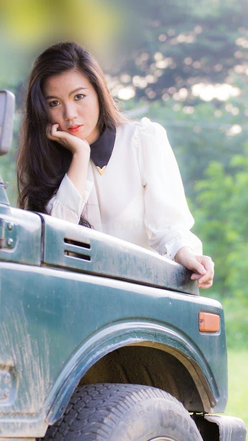 De mooie vrouw leunt op de auto, bekijkend camera royalty-vrije stock afbeelding