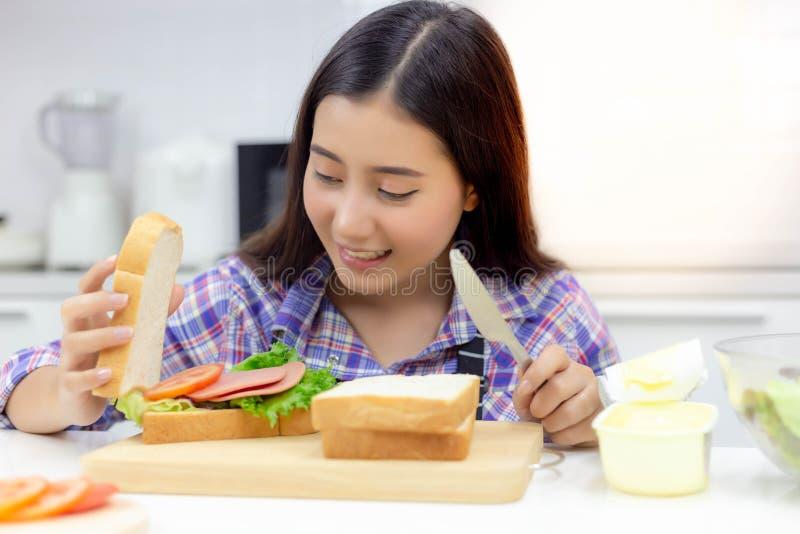 De mooie vrouw maakt of kookt sandwich in keuken voor prepar royalty-vrije stock afbeelding