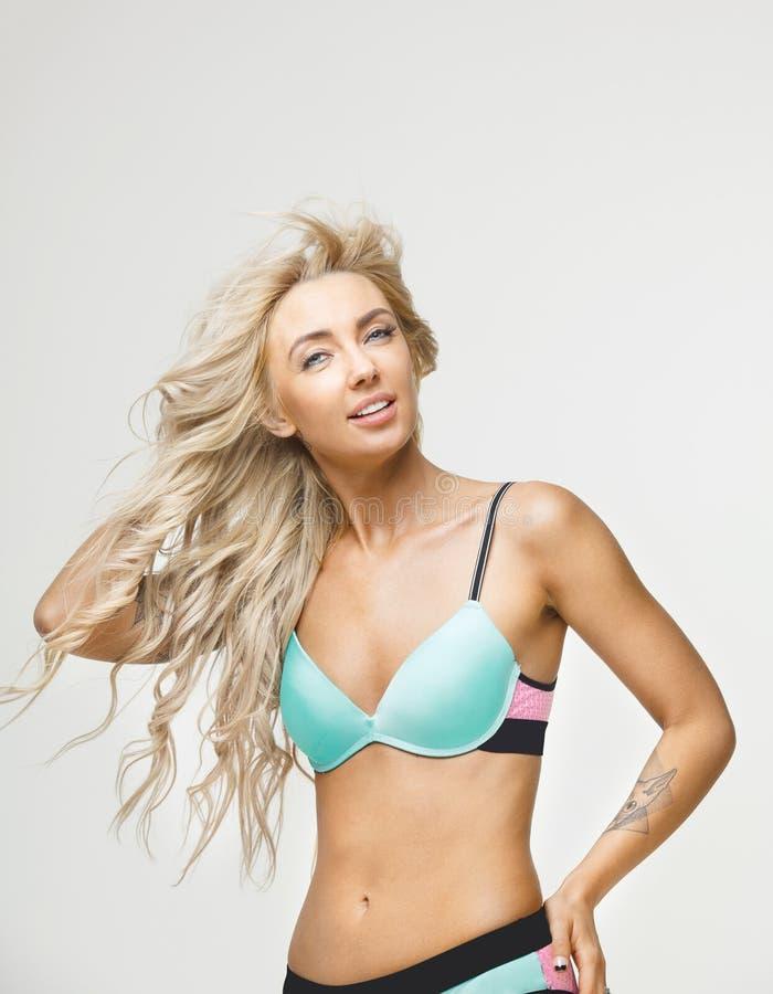 De mooie vrouw met blond haar draagt helder badpak op wit geïsoleerde achtergrond Het mooie meisje stellen in bikini bij royalty-vrije stock fotografie