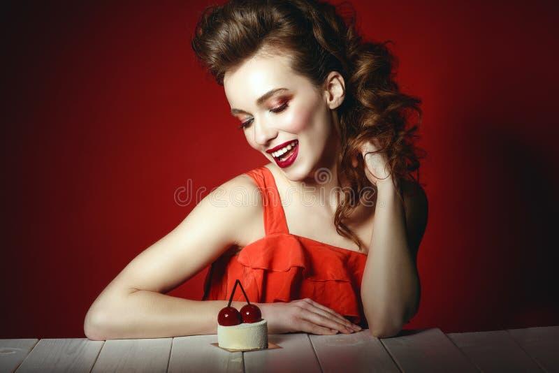 De mooie vrouw met creatief kapsel en kleurrijk maakt omhoog het zitten bij de houten lijst en het bekijken heerlijk kersengebakj stock foto