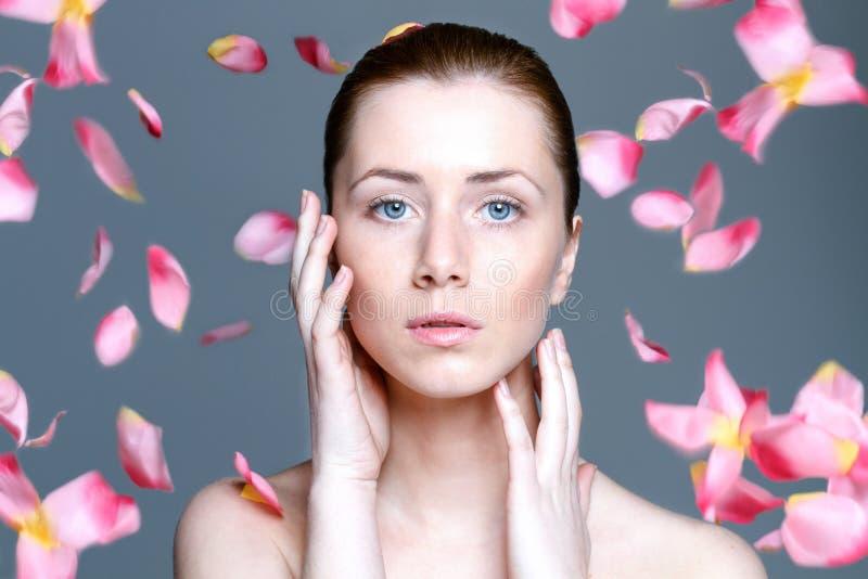 De mooie vrouw met duidelijke huid en het vallen namen bloemblaadjes toe stock foto