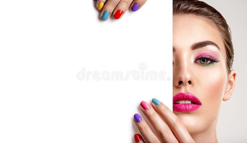 De mooie vrouw met een gekleurde manicure houdt lege affiche stock fotografie