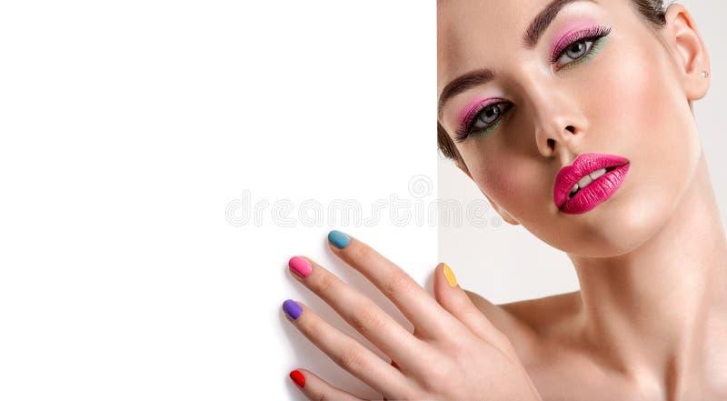 De mooie vrouw met een gekleurde manicure houdt lege affiche stock afbeelding