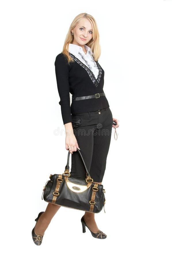 De mooie vrouw met een handtas. stock fotografie