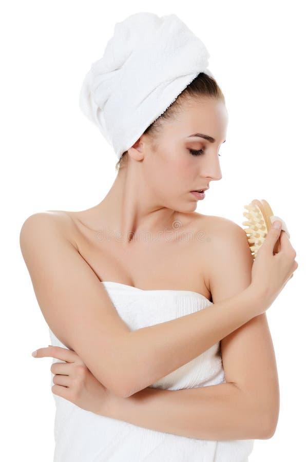Mooie vrouw met een massageborstel. Het concept van het KUUROORD. stock foto