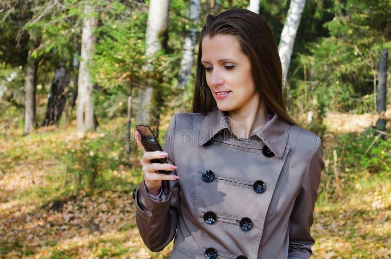 De Mooie Vrouw Met Een Mobiele Telefoon Op Gang In Hout Stock Foto