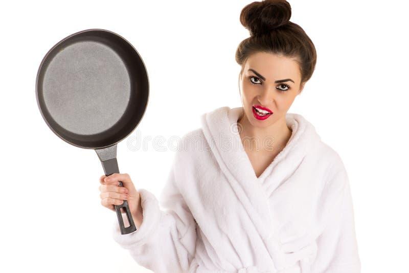 De mooie vrouw met een pan in dient witte badjas in royalty-vrije stock fotografie