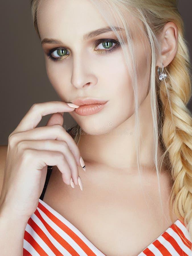 De mooie vrouw met gevlecht haar, maakt omhoog en manicure royalty-vrije stock foto