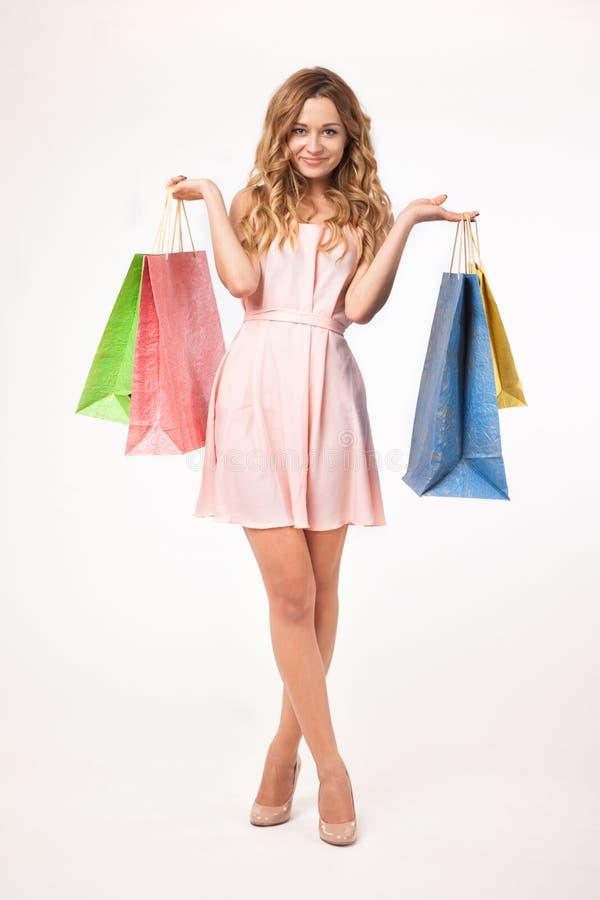 De mooie vrouw met het winkelen doet in zakken royalty-vrije stock afbeeldingen