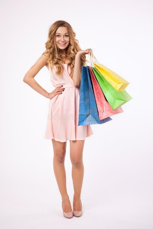 De mooie vrouw met het winkelen doet in zakken royalty-vrije stock afbeelding