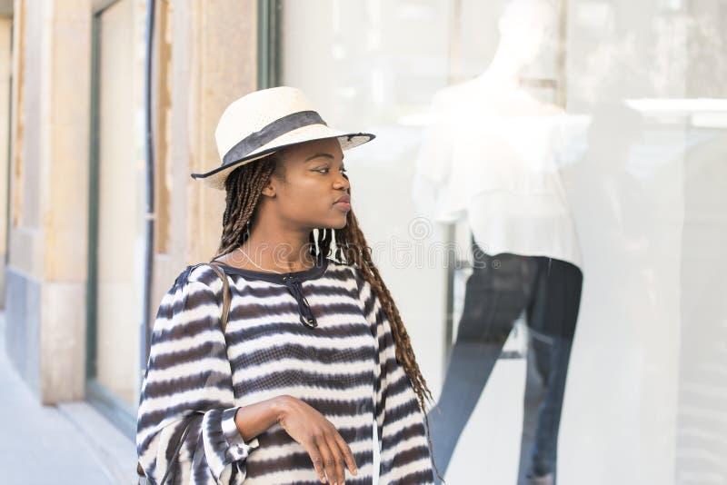 De mooie vrouw met hoed kijkt showcasekleding, winkelen het meest lifest royalty-vrije stock foto's