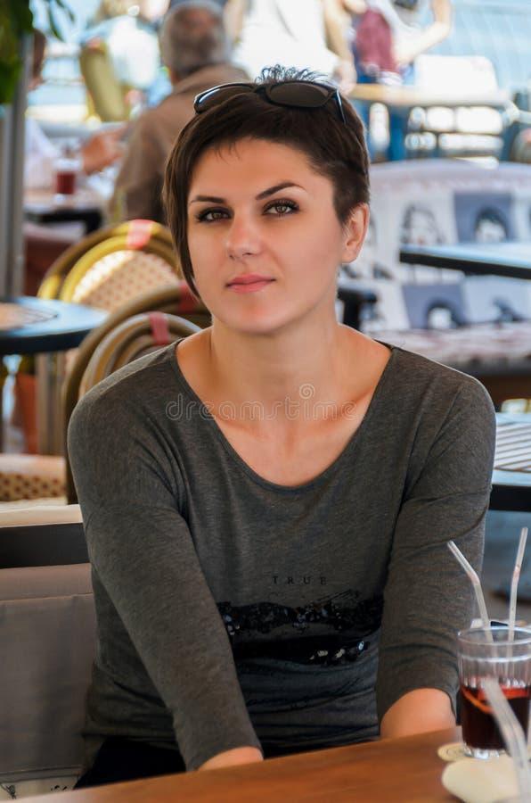 De mooie vrouw met kort kapsel zit op een de zomerterras bij a royalty-vrije stock afbeeldingen
