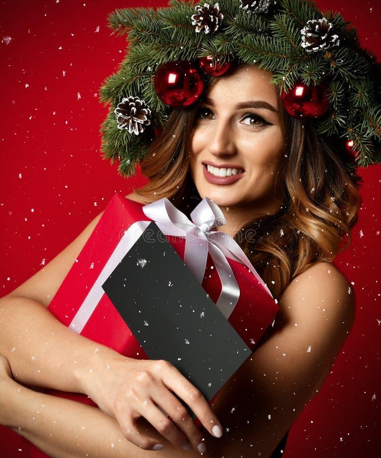 De mooie vrouw met de kroon van de Kerstmisspar met kegels en het nieuwe certificaat van de jaargift huidig onder sneeuw schilfer stock foto