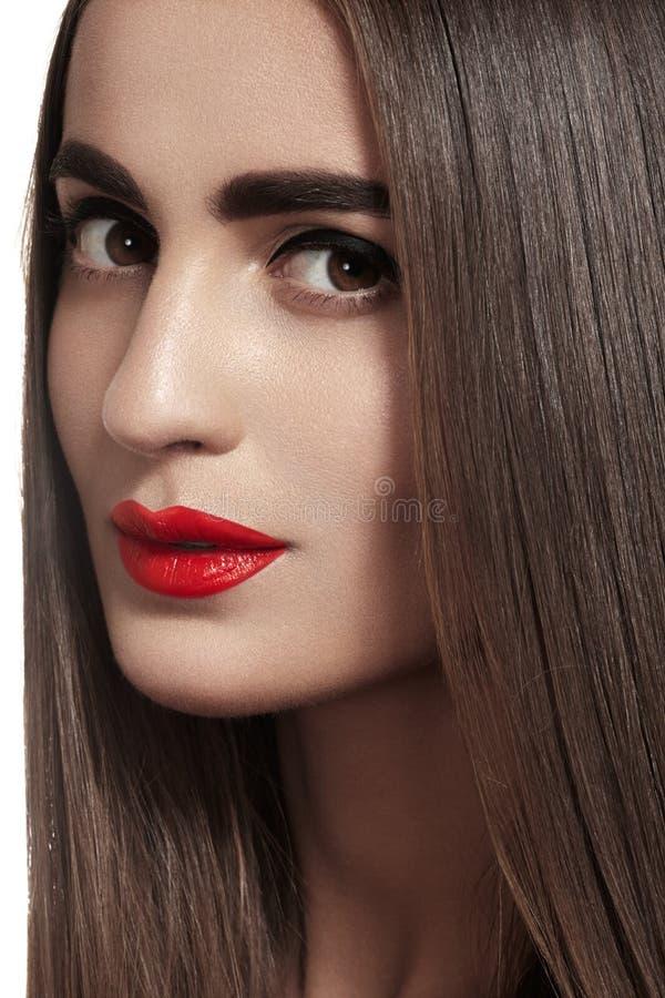De mooie vrouw met lang recht haar, de sterke wenkbrauwen & de rode lippen maken op royalty-vrije stock afbeeldingen