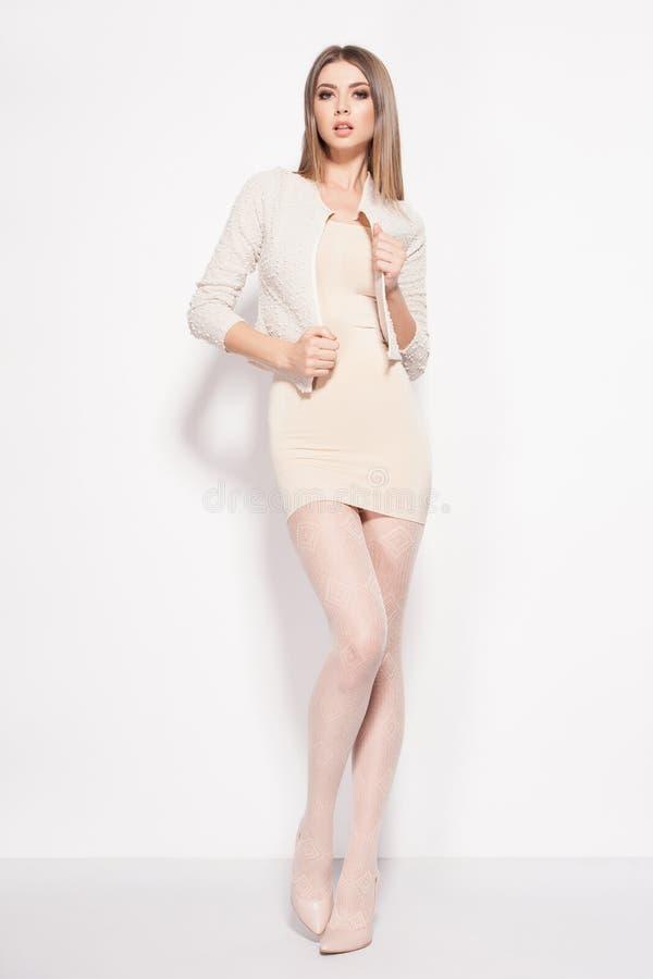 De mooie vrouw met lange sexy benen kleedde het elegante stellen in de studio