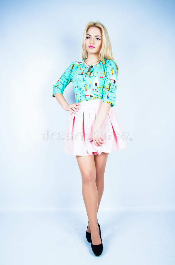 De mooie vrouw met lange sexy benen kleedde het elegante stellen in de studio stock foto