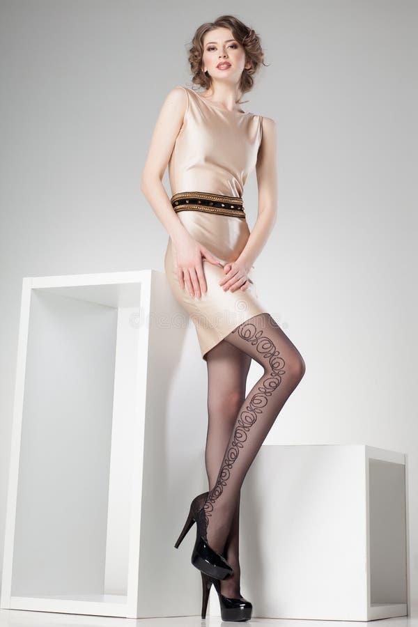 De mooie vrouw met lange sexy benen kleedde het elegante stellen in de studio - volledig lichaam stock afbeeldingen