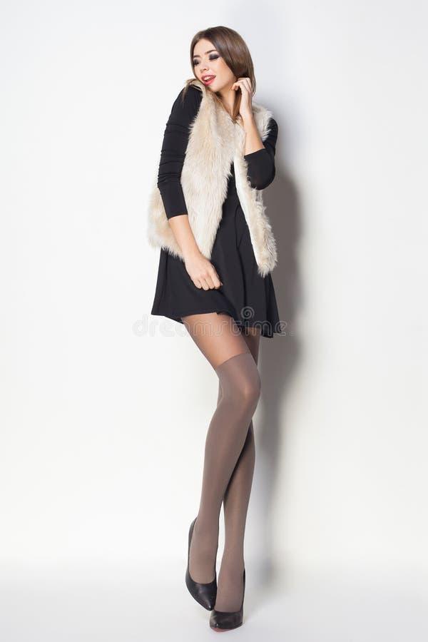 De mooie vrouw met lange sexy benen kleedde het elegante stellen in Th stock afbeelding