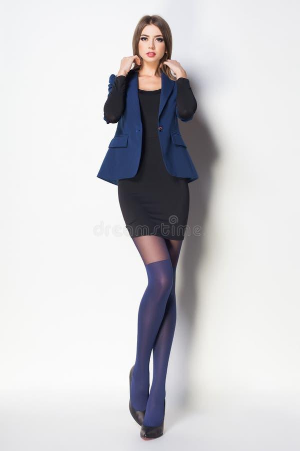 De mooie vrouw met lange sexy benen kleedde het elegante stellen in Th royalty-vrije stock afbeeldingen
