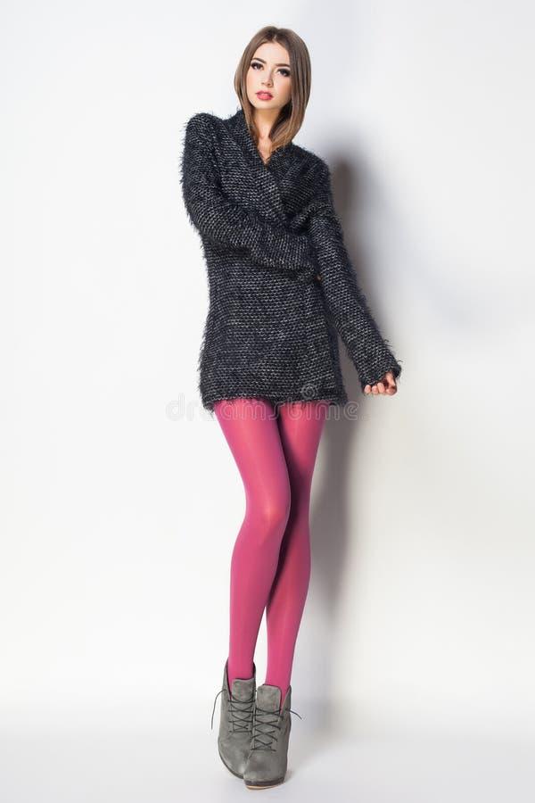 De mooie vrouw met lange sexy benen kleedde het elegante stellen in Th royalty-vrije stock foto's