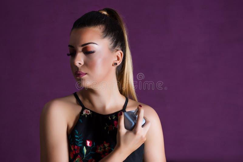 De mooie vrouw met maakt omhoog bespuitend parfum op haar hals op purpere achtergrond royalty-vrije stock foto's