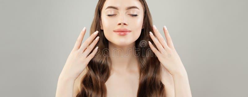 De mooie vrouw met manicured handen op grijze bannerachtergrond Natuurlijke make-up en wit nagellak op spijkers royalty-vrije stock foto