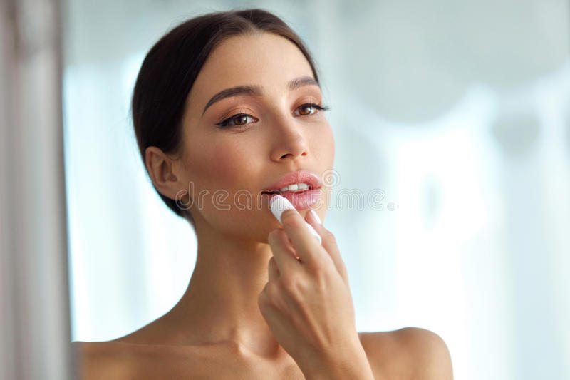 De mooie Vrouw met Schoonheidsgezicht past Balsem op Lippen toe De zorg van de huid royalty-vrije stock foto's