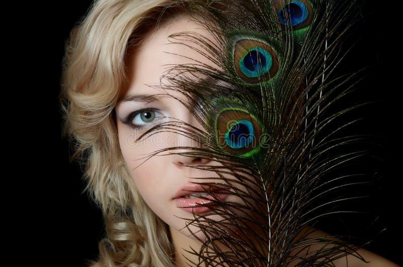 De mooie vrouw met veren van een pauw stock afbeeldingen