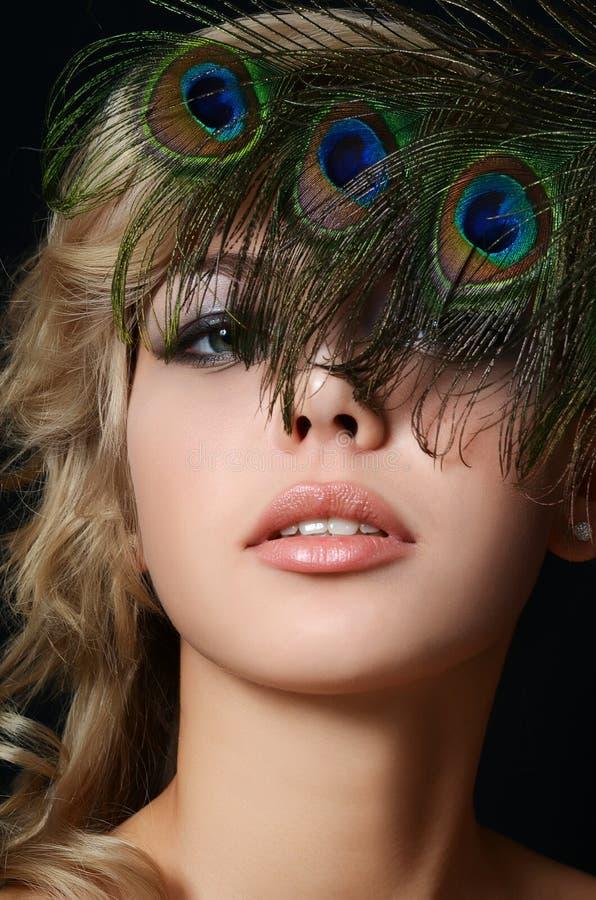 De mooie vrouw met veren van een pauw royalty-vrije stock fotografie