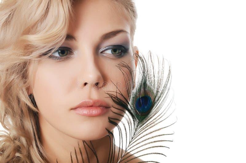 De mooie vrouw met veren van een pauw stock foto's