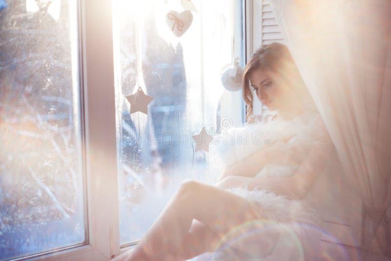 de mooie vrouw met verse dagelijkse make-up en romantisch golvend kapsel, die bij de vensterbank zitten, trekt op glas stock foto