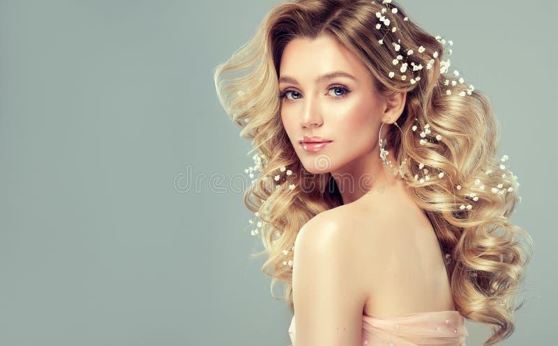 De mooie vrouw met zachte glimlach op het gezicht toont lang en krullend kapsel aan stock foto