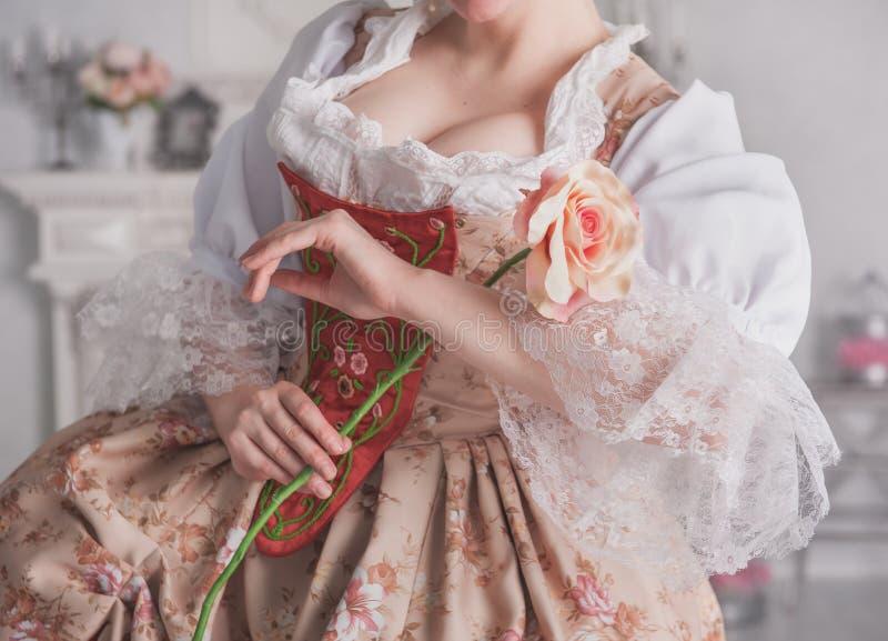 De mooie vrouw in middeleeuwse kledingsholding nam toe stock foto