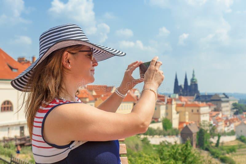 De mooie vrouw neemt pictores van het silhouet van het Kasteel van Praag stock fotografie