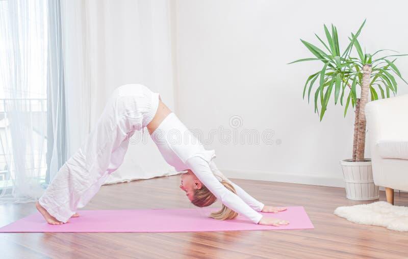 De mooie vrouw oefent thuis yoga op yogamat uit, meisje stelt de status bij Naar beneden toegekeerde hond stock foto's