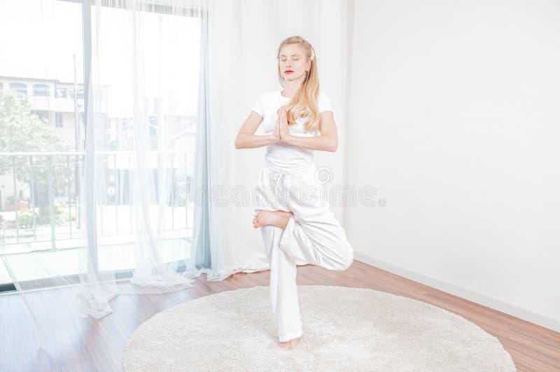 De mooie vrouw oefent yoga uit thuis, meisje die de oefening van Vrikshasana doen agains, zich bevindt in boom stel royalty-vrije stock afbeelding