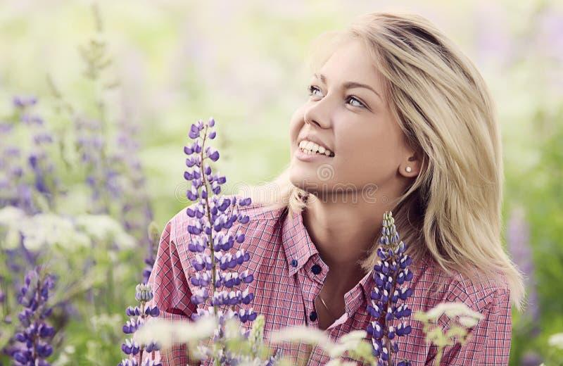 De mooie vrouw op het gebied met lupine royalty-vrije stock foto