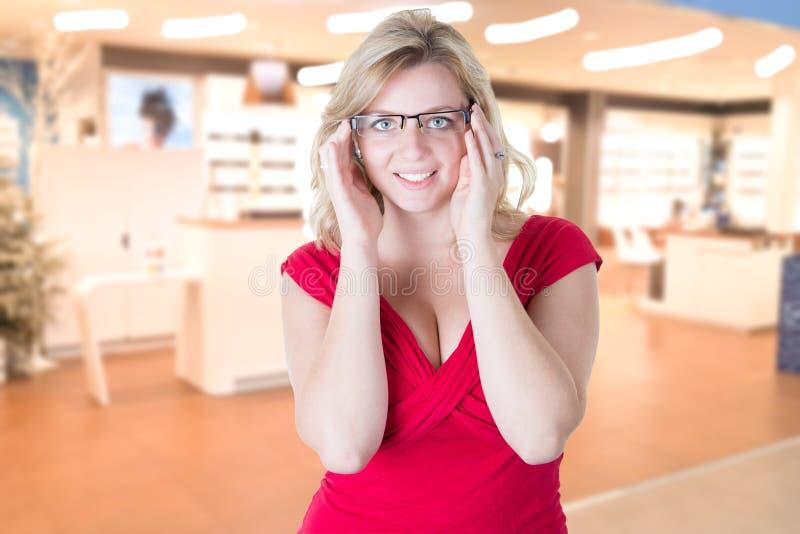 De mooie vrouw probeert een paar glazen bij oftalmoloogopticien stock afbeeldingen