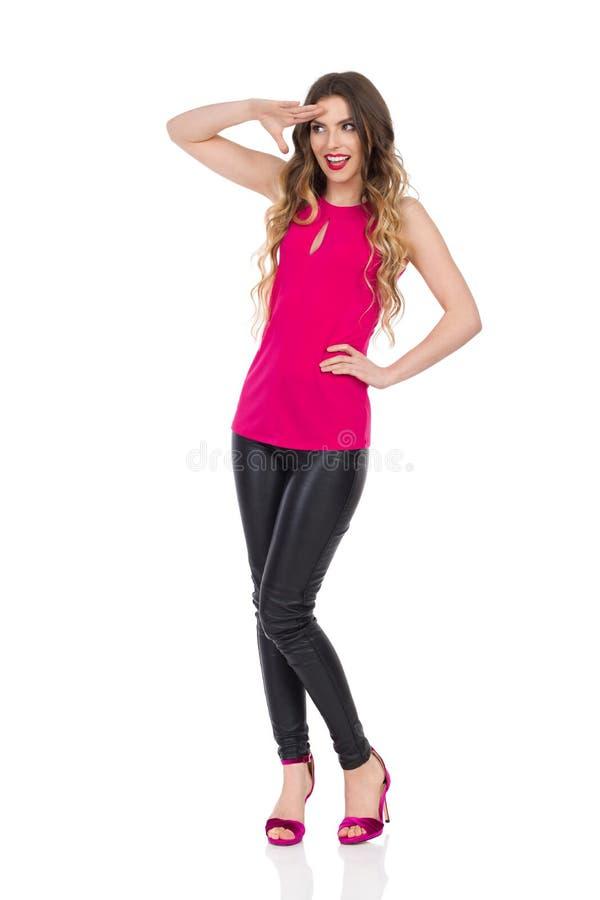 De mooie Vrouw in Roze Hoogste en Zwarte Leerbroeken groet weg en kijkt royalty-vrije stock afbeeldingen
