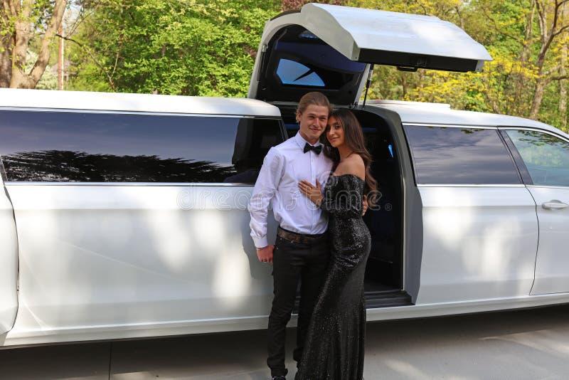De mooie vrouw in rug prom kleedt zich en knappe kerel in kostuum, sexy tiener klaar voor een luxenacht stock foto