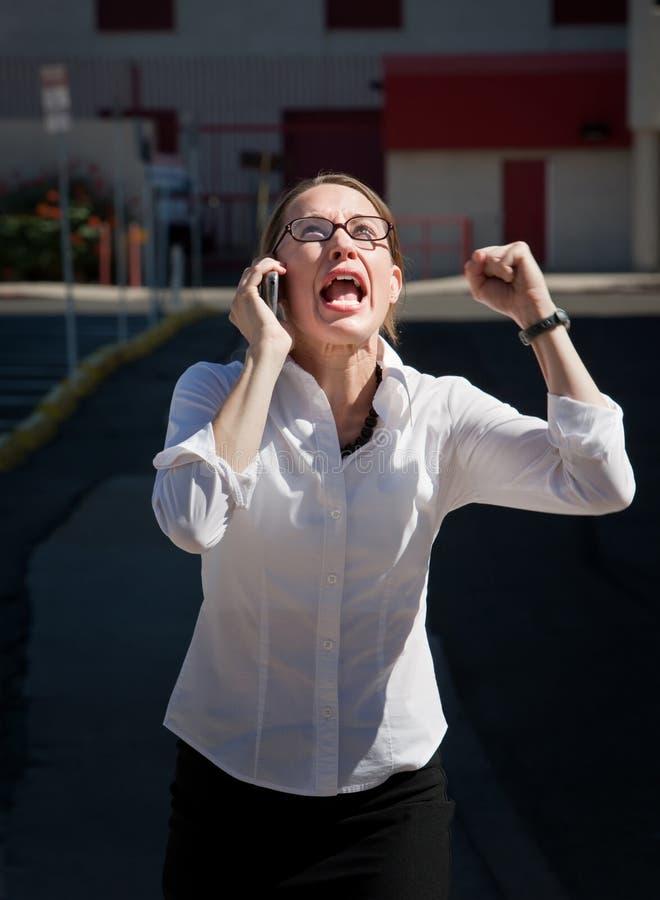 De mooie vrouw schreeuwt in celtelefoon stock foto