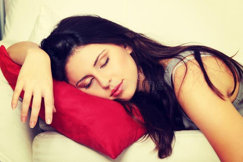 De mooie vrouw slaapt op rood hoofdkussen. stock afbeelding