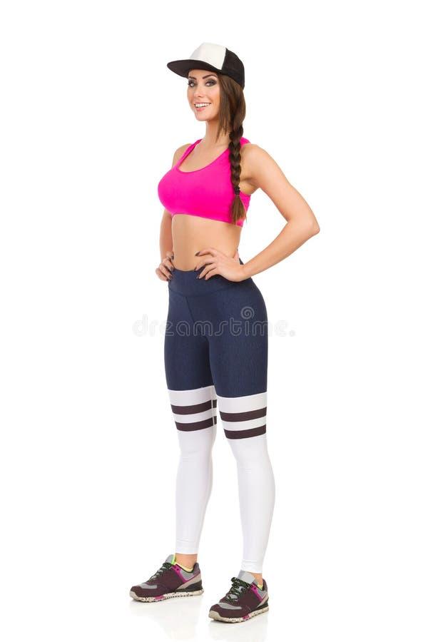 De mooie Vrouw in Sportenkleren en GLB bevindt zich en glimlacht stock afbeelding